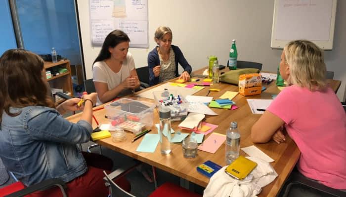 Vier Frauen sitzen am Tisch und brainstormen